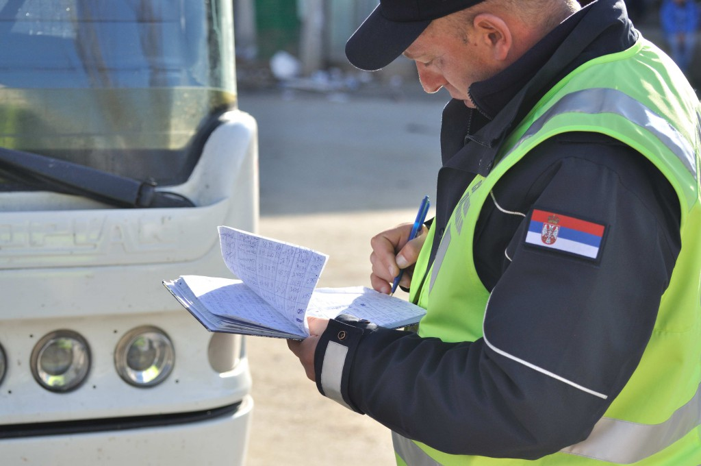 Policeman keeping track of the names of people having entered the busses